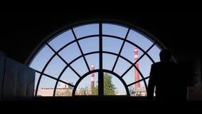 Kontur av en kraftig dominera man som ut ser ett glass fönster över staden i begrundande eller reflexion baksida lager videofilmer