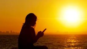 Kontur av en kvinna som använder den smarta telefonen på solnedgången stock video