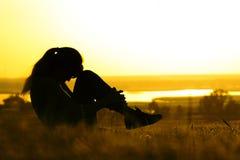 Kontur av en kvinna som gör fysiska övningar i natur på solnedgången, sportar som är kvinnliga på fältet, begrepp av sportar och  Royaltyfri Fotografi