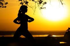 Kontur av en kvinna som gör fysiska övningar i natur på solnedgången, sportar som är kvinnliga på fältet, begrepp av sportar och  Royaltyfria Bilder