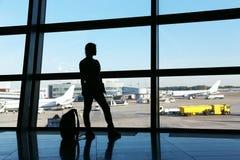 Kontur av en kvinnahandelsresande med ryggsäcken i flygplats royaltyfria bilder