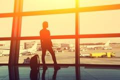 Kontur av en kvinnahandelsresande med ryggsäcken i flygplatsvardagsrum Aff?r och lopp arkivfoton