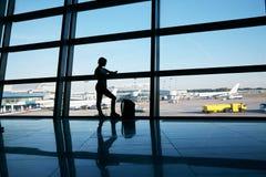 Kontur av en kvinnahandelsresande med ryggs?cken i flygplats royaltyfri foto