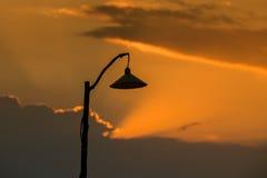 Kontur av en lampstolpe på solnedgången Royaltyfria Bilder