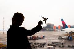 Kontur av en liten flygplanmodell på flygplats i ungehänder Royaltyfria Foton