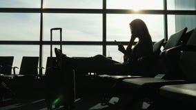 Kontur av en lyckad kvinna i flygplatsterminalen När du väntar på flyget använder en smartphone och hörlurar fotografering för bildbyråer