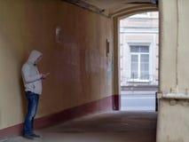 Kontur av en man i en huv i den gamla borggårdbågen royaltyfria bilder