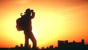 Kontur av en man med en ryggsäck mot ljus himmelsolnedgång arkivfilmer