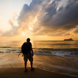 Kontur av en man med en ryggsäck på soluppgång Arkivfoto