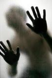 Kontur av en man med händer på ett frostat exponeringsglas arkivfoton