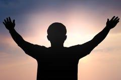 Kontur av en man med handen upp på solnedgångbakgrund Arkivbilder