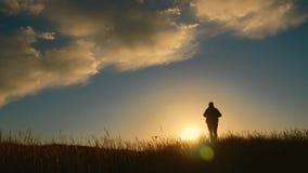 Kontur av en man med en ryggsäck mot ljus himmelsolnedgång Sun går besegrar för dublin för bilstadsbegrepp litet lopp översikt Tu lager videofilmer