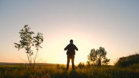 Kontur av en man med en ryggsäck mot ljus himmelsolnedgång Sun går besegrar för dublin för bilstadsbegrepp litet lopp översikt Tu stock video