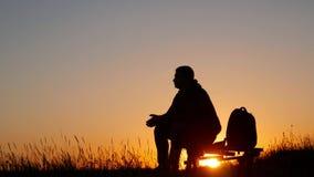 Kontur av en man med en ryggsäck mot ljus himmelsolnedgång Sun går besegrar för dublin för bilstadsbegrepp litet lopp översikt Tu arkivfilmer