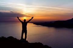 Kontur av en man på bakgrunden av solnedgångsolen i havet royaltyfri bild