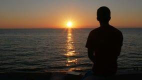 Kontur av en man på solnedgången på stranden av havet En man beundrar den orange solen är nästan fastställd arkivfilmer