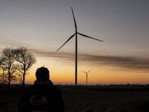Kontur av en man på solnedgången som gör ett foto av vindturbiner Vindkraftväxter på solnedgången royaltyfri bild