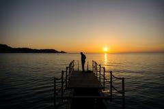 Kontur av en man som får klar för att simma i sjösida på solnedgång royaltyfri bild