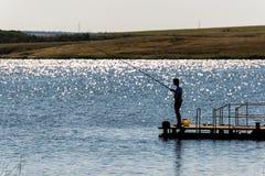 Kontur av en man som fiskar Fotografering för Bildbyråer