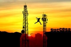 Kontur av en man som hoppar över klippan och telekommunikationen Royaltyfri Fotografi