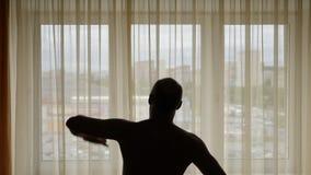 Kontur av en man som inomhus utför övning I bakgrundsstadsgatan bak fönstergardiner Män som värmer upp gör stock video