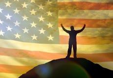 Kontur av en man som rymmer hans händer upp på överkanten av ett berg, mot bakgrunden av himlen av flaggan av Amerika, USA royaltyfria bilder