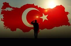 Kontur av en man som saluterar mot den turkiska flaggan arkivbild