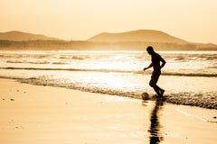 Kontur av en man som spelar fotbollfotboll på solnedgången Famara strand, Lanzarote, kanariefågelöar, Spanien Arkivbilder
