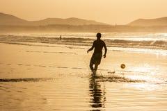 Kontur av en man som spelar fotbollfotboll på solnedgången Famara strand, Lanzarote, kanariefågelöar, Spanien Arkivfoto