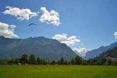 Kontur av en paraglider över bergen som täckas med skogen royaltyfri bild
