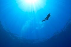 Kontur av en Snorkeller med solstrålar bakom arkivfoton