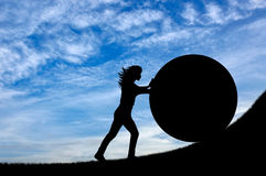 Kontur av en stark kvinna som skjuter upp en sten Arkivfoto