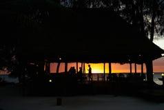 Kontur av en strandstång mot en romantisk solnedgång royaltyfria bilder