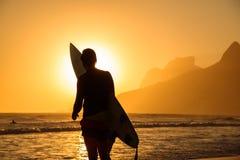 Kontur av en surfare som rymmer hans surfingbräda på bakgrunden av den guld- solnedgången på den Ipanema stranden, Rio de Janeiro arkivfoton
