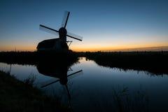 Kontur av en traditionell holländsk väderkvarn mot aftonhimlen arkivbild