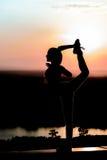 Kontur av en ung flicka på solnedgångbakgrunden Arkivbild