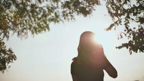 Kontur av en ung flicka som talar på telefonen på solnedgången arkivfilmer