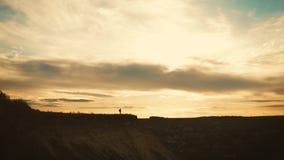 Kontur av en ung fotvandrareflicka med berg f?r en ryggs?ck ?verst p? solnedg?ngen arkivfilmer
