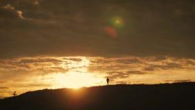 Kontur av en ung fotvandrareflicka med berg f?r en ryggs?ck ?verst p? solnedg?ngen stock video