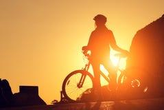 Kontur av en ung kvinna på en cykel på solnedgången Arkivfoton
