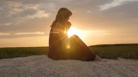 Kontur av en ung kvinna på sanden på solnedgången, flicka som ber till guden på horisont, begreppet av semestrar, religion, beaen lager videofilmer