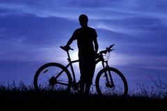 Kontur av en ung man med en cykel på solnedgången arkivbilder