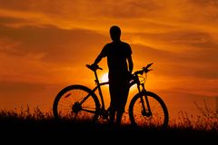 Kontur av en ung man med en cykel på solnedgången arkivbild