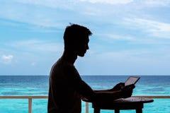 Kontur av en ung man som arbetar med en minnestavla p? en tabell Klart bl?tt tropiskt vatten som bakgrund arkivbild