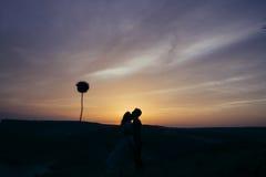 Kontur av ett älska par som kysser i solnedgången Arkivbild