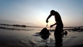 Kontur av ett barn på stranden som bygger en sandslott på solnedgången arkivfilmer