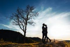 Kontur av ett förälskat par Grabb och flicka som kramar på solnedgången Koppla ihop resor Vänner i natur Hålla ögonen på för man  fotografering för bildbyråer