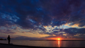 Kontur av ett fiskareanseende på ett solnedgångbakgrundslandskap Arkivfoton