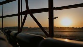Kontur av ett flygplan som tar av på solnedgången på Pekingflygplatsen i bakgrunden av ett fönster
