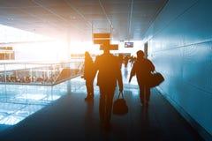 Kontur av ett oigenkännligt affärsresandefolk på den internationella flygplatsen Royaltyfri Bild
